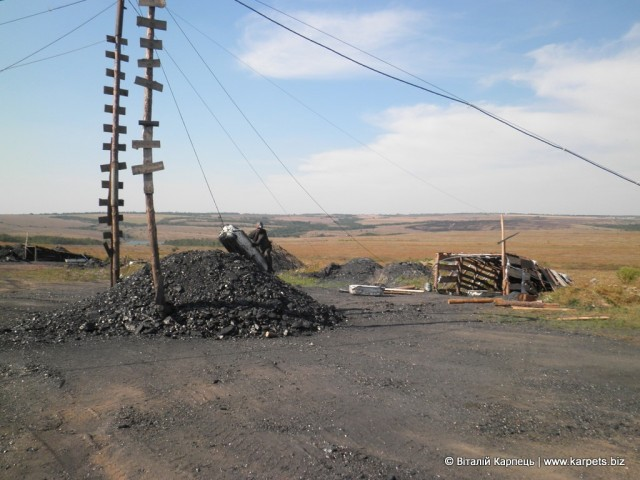 Шахтар виїжджає з-під землі на човнику, наповненому вугіллям