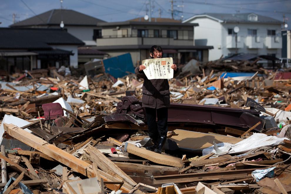 Префектура Міягі, жінка радіє знайденому випускному сертифікату її доньки посеред уламків їх будинку. (Yasuyoshi Chiba/AFP)