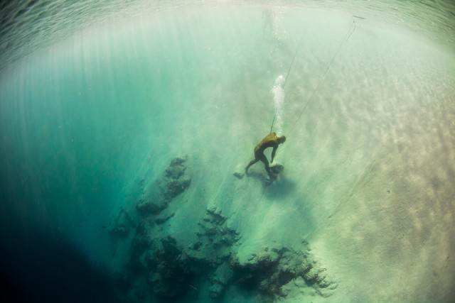 Alexey Molchanov stands on the edge of Dean's Blue Hole after his 95 meter constant weight No-fins dive at Vertical Blue 2014.