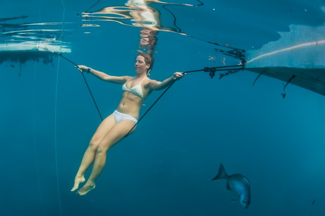 Fish swim around a woman swinging underwater on a rope attached to two platforms inside of Dean's Blue Hole on Long Island, Bahamas.