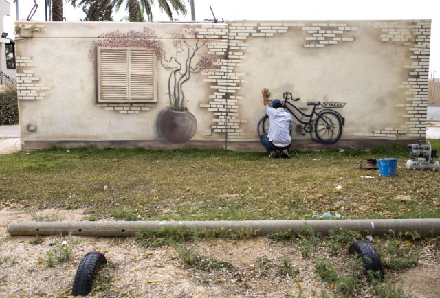 Israeli artist Eliasaf Myara paints a mural on a concrete protective shelter in the village of Shokeda, located a few kilometers from the border with the Gaza Strip, Israel, 25 June 2015. The Israeli Defense Ministry has placed hundreds of small concrete protective shelters to all towns located near the Gaza Strip to protect its citizens from incoming rockets. On 08 July 2015, Israel will mark one year since the 2014 Israel–Gaza conflict, also known as Operation Protective Edge.
