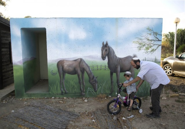 An Israeli helps his son to ride a bicycle next to a concrete protective shelter painted by Israeli artist Eliasaf Myara in the village of Shokeda, located a few kilometers from the border with the Gaza Strip, Israel, 14 June 2015. The Israeli Defense Ministry has placed hundreds of small concrete protective shelters to all towns located near the Gaza Strip to protect its citizens from incoming rockets. On 08 July 2015, Israel will mark one year since the 2014 Israel–Gaza conflict, also known as Operation Protective Edge.